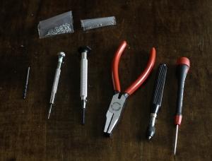 """Poranterä, """"Tap""""-työkalu, """"star-nut spanner"""", """"de-riveting""""-työkalu, """"universal holder"""" ja ruuvimeisseli. Ylhäällä vaihtoruuveja ja vastakappaleita."""